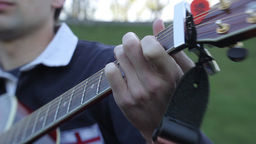 The hand of the guitarist on the guitar fretboard pulls the strings Footage