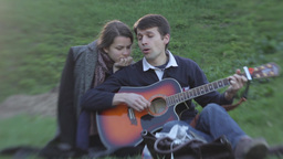 The guy sings and plays guitar for the girl in the Park Footage