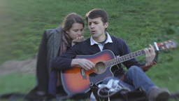 The guy sings and plays guitar for the girl in the Park Stock Video Footage