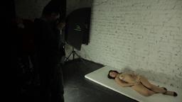 Girl model posing naked lying on the floor of the photo Studio Footage