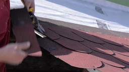 Male worker with a sharp scissors cut pieces of roofing situated on a roof 01 Live Action