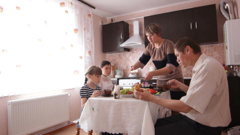 Camera Shows Family Dining in Kitchen with Modern Furniture Live Action