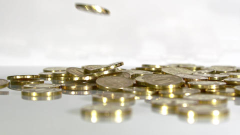 Coins fall on a white, slow-motion shot ビデオ