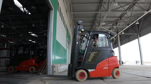 Side View Modern Forklift Drives and Workers Go into Warehouse Footage