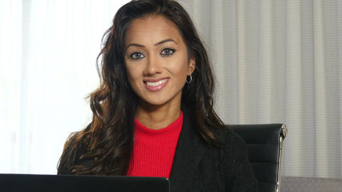 Happy smiling ethnic businesswoman working in an office Footage