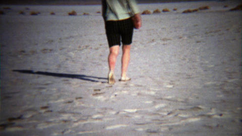 1971: Women walking on white salty dry lake bed in flat shoes Footage