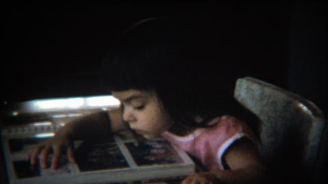 1971: Young girl looks at family photograph album scrapbook Footage