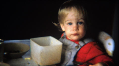 1971: Toddler boy eats cereal from square tupperware bowl Footage