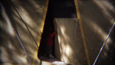 1971: Toddler cautiously entering big outdoor camping tent Footage