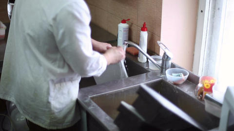 The kitchen staff washes the dishes Live Action