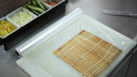 A sushi chef prepares the bamboo mat to tighten the roll Footage