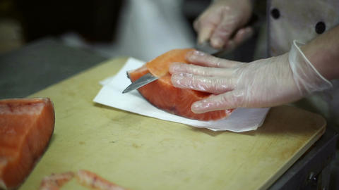 The chef cuts knife a fillet of red fish Live Action