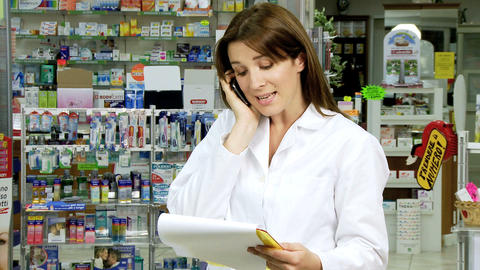 Pharmacist on the phone with client in pharmacy Stock Video Footage