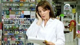 Pharmacist On The Phone With Client In Pharmacy stock footage