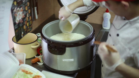 The chef pours vinegar mixture into the rice Footage