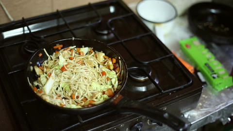 Noodles with meat and vegetables are fried in the frying pan Footage