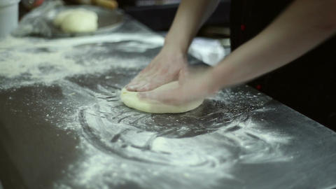 The chef rolls out the dough with a rolling pin Live Action