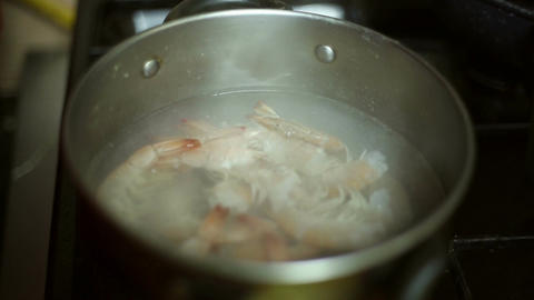 Boil water in a saucepan and pour prawns Footage