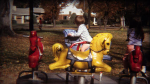 1971: Kids play on merry go round carousel in autumn fallen leaves Footage