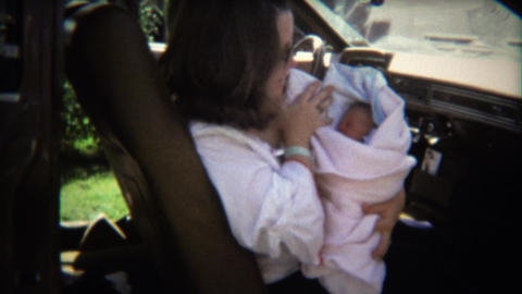 1970: Mom in car brings newborn baby boy home from hospital Footage