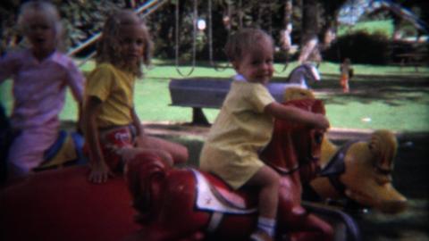 1971: Kids on merry go round outdoor playground fun ride Footage