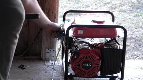 Man revolves or press some buttons on a gasoline generator Footage