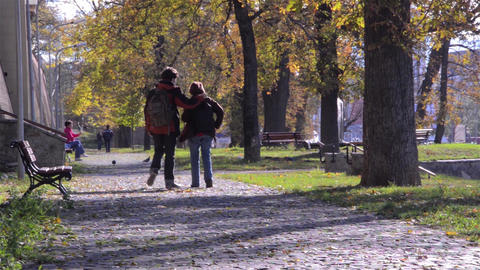 Two young men walking in a park, in a beautiful and sunny autumn day 68 Footage