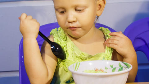 closeup little blonde girl eats soup vegetables Footage