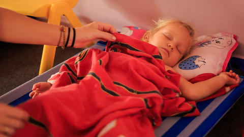 Little Blond Girl Sleeps on Bed under Red Blanket Footage