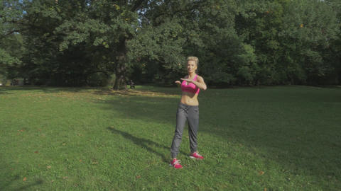 Fit woman stretching in the summer park Filmmaterial
