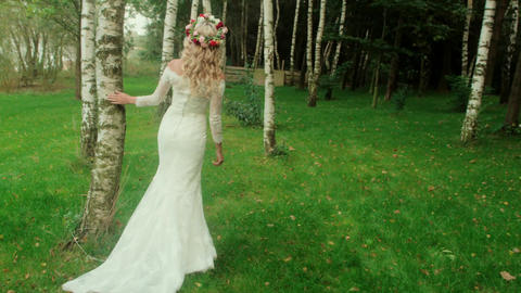Pretty bride walking among trees - slow motion Filmmaterial