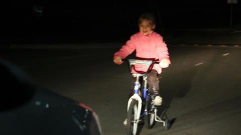 Little Girl Rides Bike along Dark Road Car Drives Past Footage