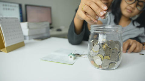 Asian little girl and mother putting coins to the glass jar saving money for hom Footage