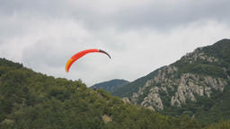 View of a tandem paraglider above the mountain valley. Flying in tandem Footage