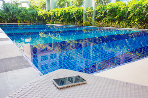 Smartphone put on armchair beside the pool Photo