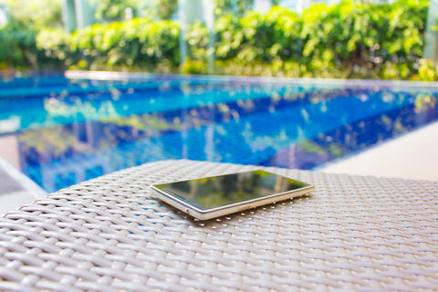 Smartphone put on armchair beside the pool フォト