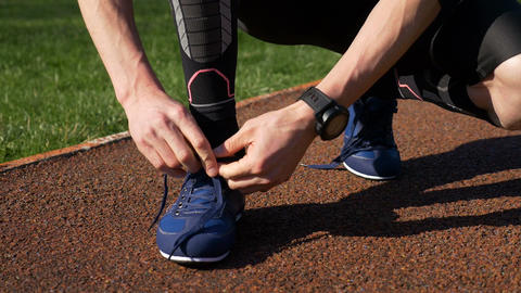 Fit jogger tying both shoelaces before running practice on track race Footage