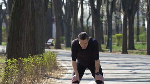 Fit jogger running in park taking a break and setting his fitness tracker smart  Footage