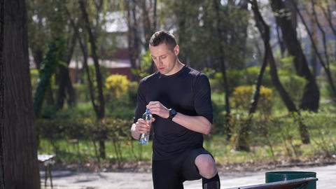 Slow motion of exhausted jogger drinking water from bottle after finishing his t Footage