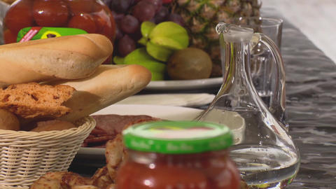 Table with decanter, baguette, fried chiken, salami and fruits Footage