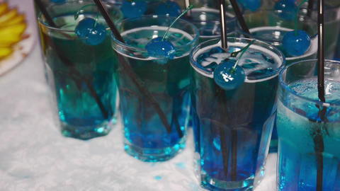 Glasses fool of blue cocktail with tubules and blue cherries Footage