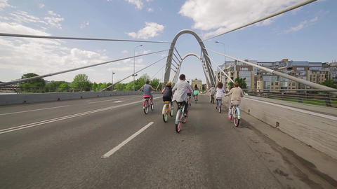 Back side of cycling group of people across bridge in summer cloudness day Footage