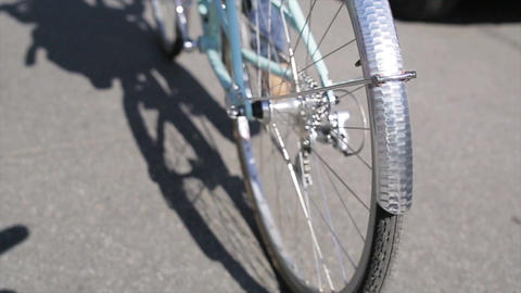 Back side of person cycling in summer day wheel of bicycle focus in. Slow motion Footage