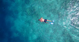 v06446 Aerial flying drone view of Maldives white sandy beach young people snork Footage