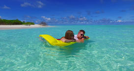 v07264 4k Maldives white sandy beach 2 people young couple man woman floating on Footage