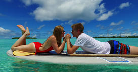 v07320 Maldives white sandy beach 2 people young couple man woman paddleboard ro Filmmaterial