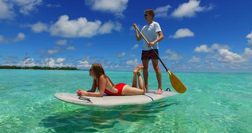 v07370 Maldives white sandy beach 2 people young couple man woman paddleboard ro Foto