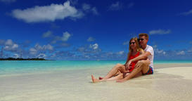 v07428 Maldives white sandy beach 2 people a young couple man woman sitting toge Footage