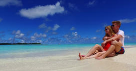 v07430 Maldives white sandy beach 2 people a young couple man woman sitting toge Filmmaterial
