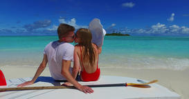 v07447 Maldives white sandy beach 2 people a young couple man woman sitting toge Footage